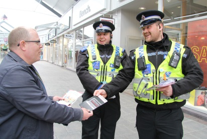 Two PCSOs speak to a man about online safety at an event at McArthur Glen Bridgend
